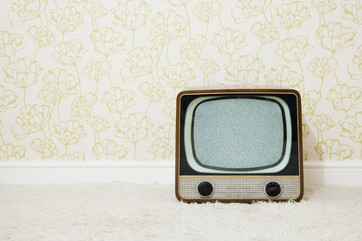 Retro television in room with patterned wallpaper